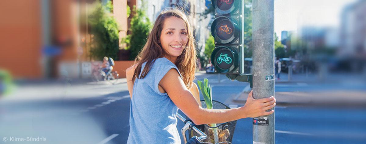 Frau auf Rad steht an einer Ampel