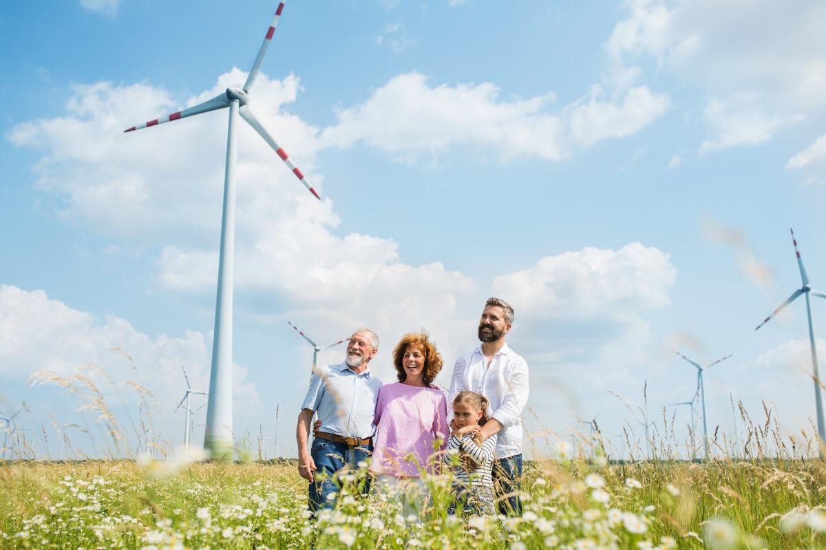 Familie auf Feld vor Windpark