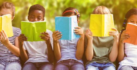 Kinder sitzen vor Büchern und lesen