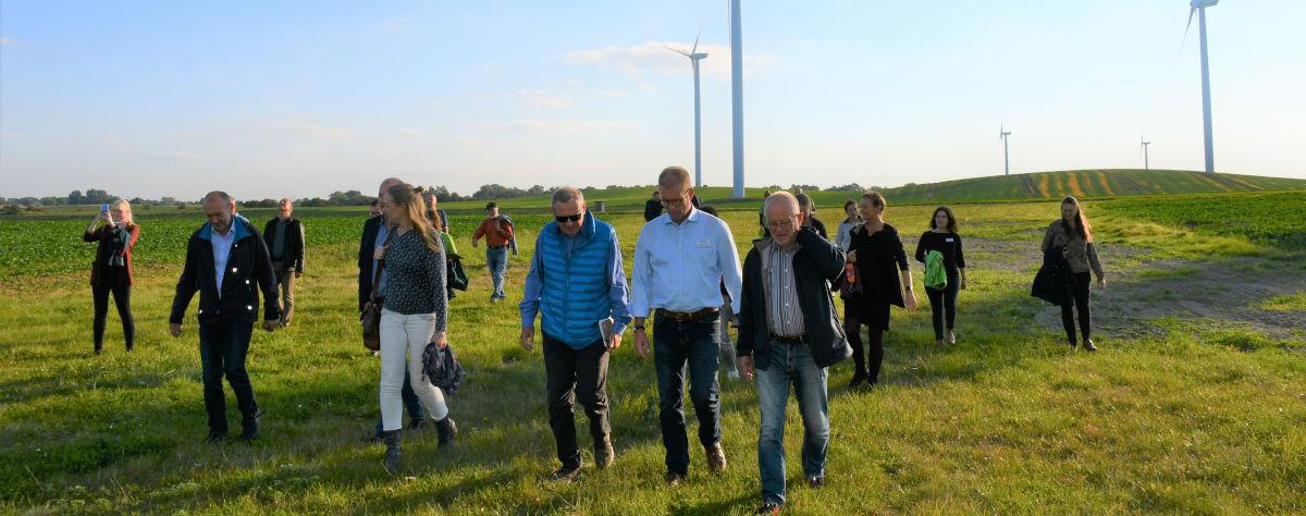 Teilnehmer vor Windrädern auf Feld